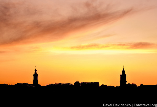Towm steeple stands silhouetted against a vibrant orange sky.